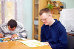 Man with autism engages in self study, in rehabilitation center
